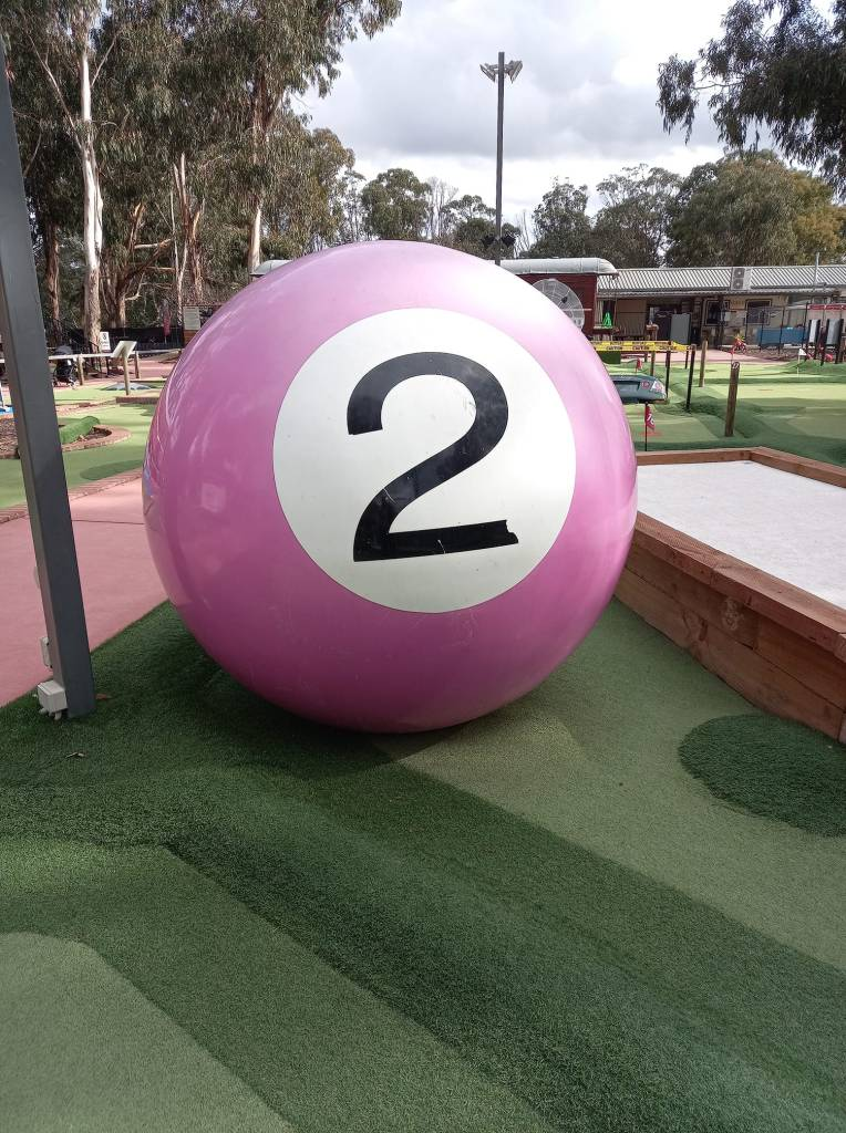 the big pool ball is a giant replica of a real pool ball. it is pink with the number 2 on it