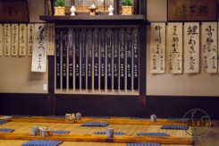 The back wall of the Komakata Dozeu restaurant in Asakusa, Tokyo, Japan, hung with caligraphy paper posters and traditional decorations | BIG tiny World Travel