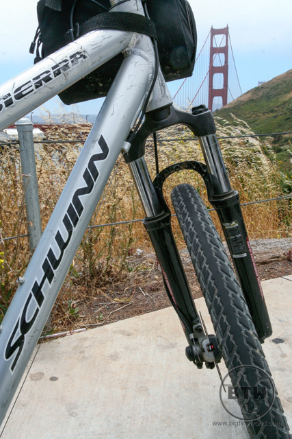 A low-angle view of a bike in front of the Golden Gate Bridge | BIG tiny World Travel