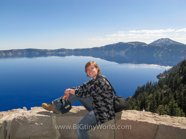 Brianna sitting on an overlook to Crater Lake | BIGtinyWorld Travel