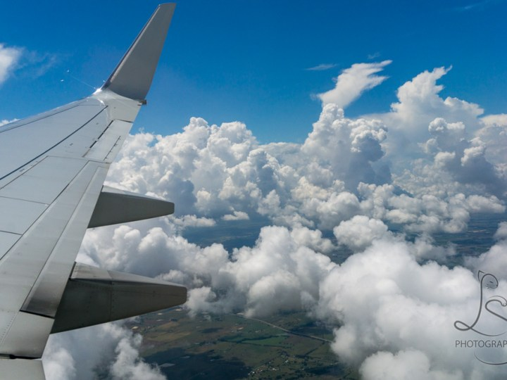 Puffy clouds floating by our airplane's wing | BIG tiny World Travel
