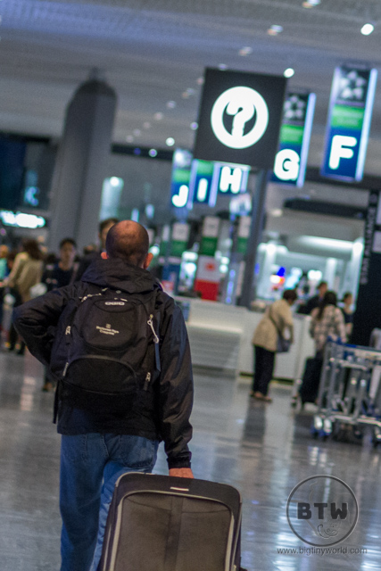 Aaron wheeling a suitcase through an airport lobby | BIG tiny World Travel
