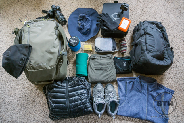 A flat lay of travel gear, including clothing, camera gear, shoes, and bags | BIG tiny World Travel