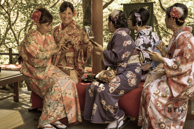 Women in flowery kimono looking at a cell phone at the Kiyoumizu Temple in Kyoto, Japan