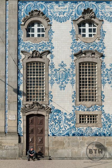 Aaron sitting in front of the azulejos on the wall of the Igreja do Carmo church in Porto, Portugal