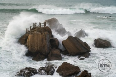 Large wave crashing over a rock at Santa Cruz Beach