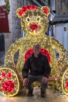 Aaron sitting in front of a giant Christmas bear in Dubrovnik, Croatia