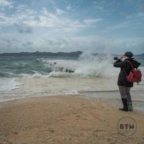 A woman photographing the waves Zadar, Croatia