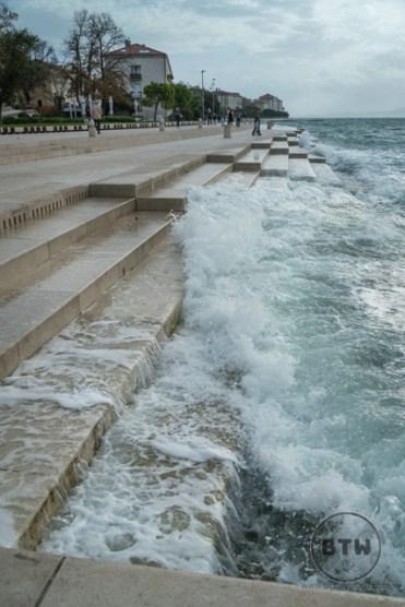A wave crashing into the stairs at the Sea Organ in Zadar, Croatia