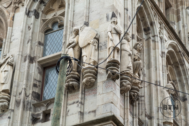 Statues carved into a building wall in Cologne, Germany