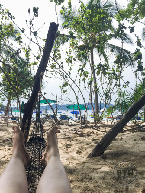 Feet on a hammock, with trees and a Costa Rica beach in the background