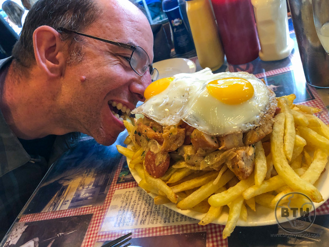 Aaron grabbing a french fry with his teeth from a massive pobre dish in Chile