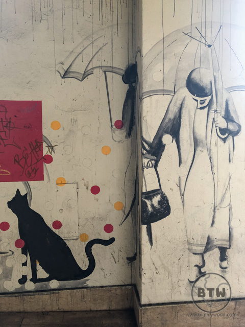 Street art in Rijeka, Croatia depicting a cat and a woman under an umbrella in the rain