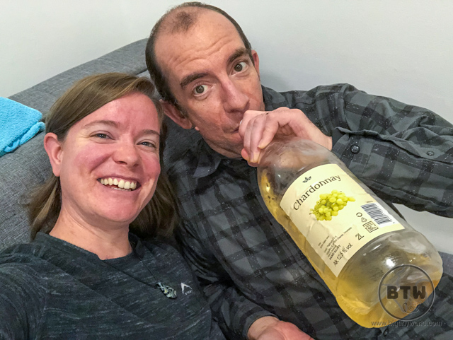 Brianna sitting with Aaron as he pretends to guzzle a massive bottle of chardonnay