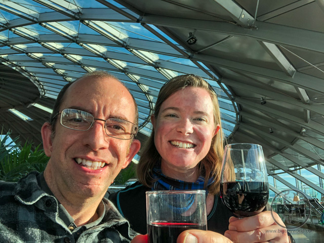 Aaron and Brianna sipping wine in an airport lounge in Basel, Switzerland