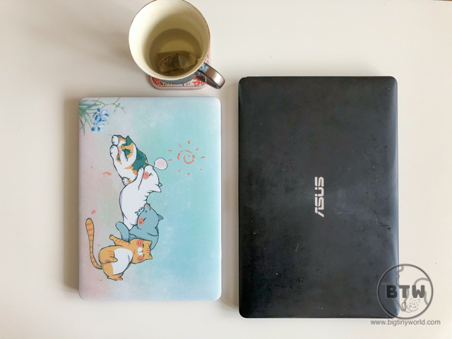 Two laptops with a spent cup of tea