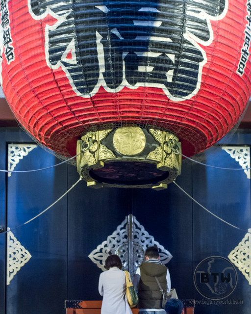 Two people praying under a large red lantern at a shrine in Tokyo, Japan