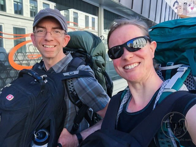 Aaron and Brianna, each wearing two backpacks on a city street in Norway | BIG tiny World Travel