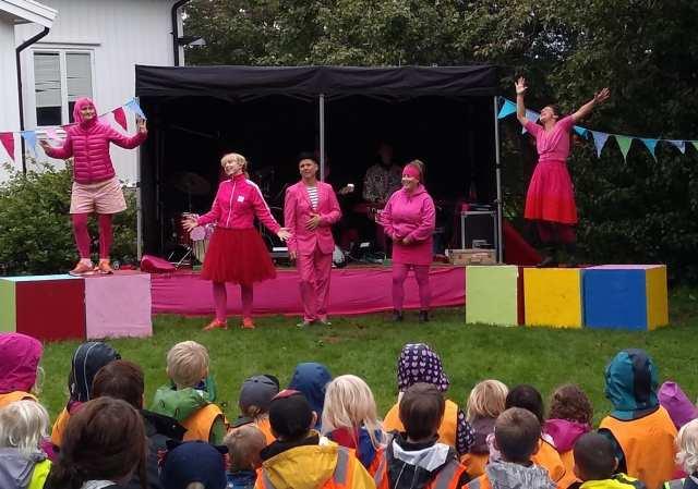 Sångnummer i en trädgård. Alla har rosa kläder.