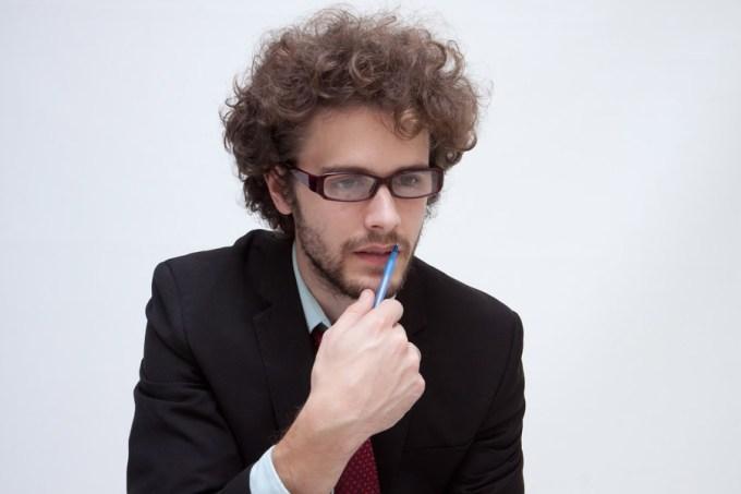ボールペンを持って考え込むビジネスマン