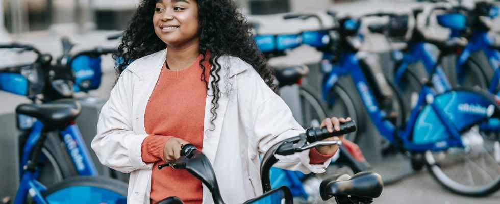 smiling black woman walking with bicycle along street renting station