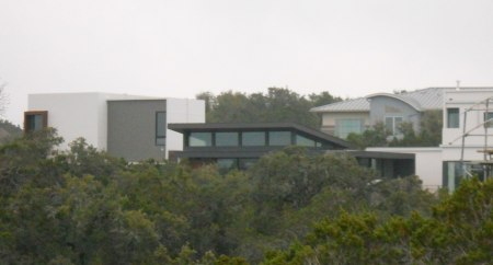 An ultra-modern house peeks out over the cedars and live oaks.