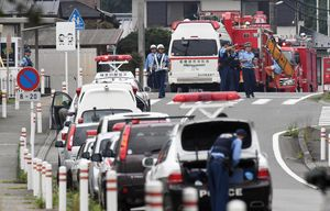 Police officers stand by with ambulances and firetrucks seen on a street near a facility for the handicapped where a number of people were killed and dozens injured in a knife attack Tuesday, July 26, 2016, in Sagamihara, outside Tokyo. (Kyodo News via AP)