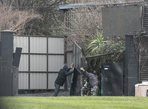Raid: Workmen remove broken gates at the biker gang's 'compound' in Crumlin