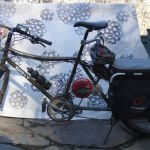 """My bike is a Surly Big Dummy Xtracycle with Stokemonkey motor, described in detail elsewhere. I named it """"The Spirit of Ithaca"""". I've changed so many parts it's hard to give it a value, but you could probably get a comparable electric cargo bike for $3,000. Bicyclists may notice that my bike has an unusually large chainring. Last year I doubled the voltage of the motor from 36 to 72v, making my bike much more powerful—it can carry two adults up the steepest hills in Ithaca. Since by design the Stokemonkey motor moves the pedals, the increased power increased the speed of the pedals and it became necessary to increase the size of the chainrings to slow down the pedals."""