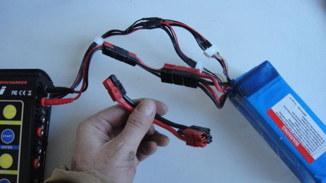 "Thea and JJ's bikes both use two 18.5v lipo batteries connected in series for a 37v battery pack. The RC charger, however, needs to charge them in parallel at 18.5v. I made special connectors to switch the batteries between serial and parallel, similar to the lead-acid battery connectors described in a previous post. In this photo the parallel connector is on the top connected to the battery and the serial is on the bottom in my hand. In addition to the power output connectors, lipo batteries have ""balance"" connectors to enable the charger to manage each cell individually. This photo shows a parallel balance connector I made so that I can charge a 37v battery from one charging port."