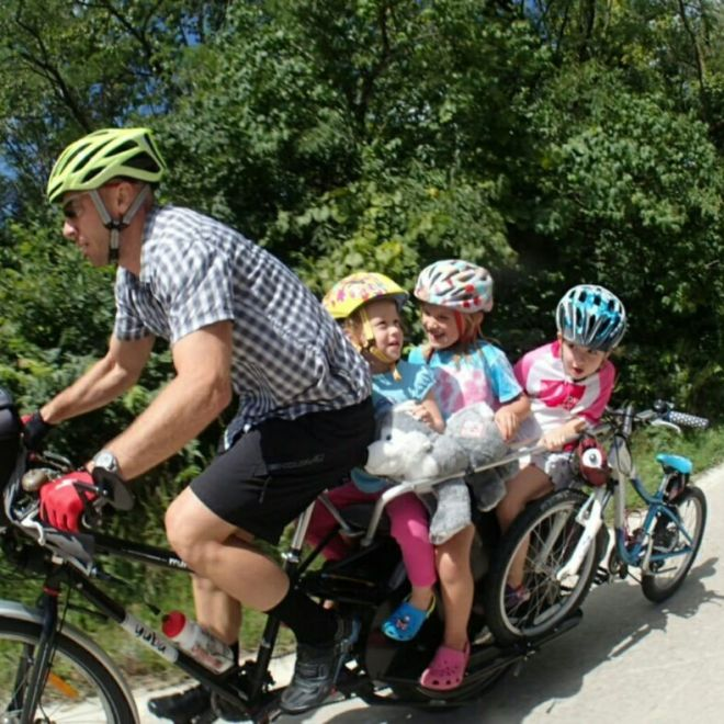 """Don Galligher carrying three girls and a 20"""" bike up a hill"""