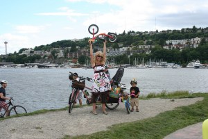Madeleine Carson, Seattle, WA, at the waterfront with her kids and bike, holding a kid's bike overhead.