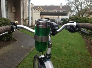 Handlebar-mounted coffee cup holder for a bike.
