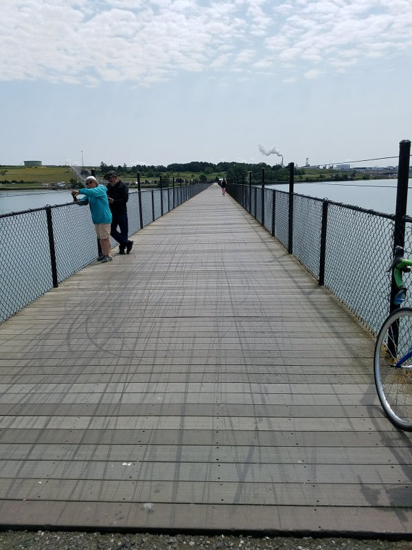 Long wooden trestle with decking, two people leaning over fence at left.