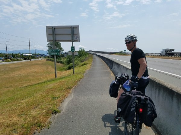 Man with bicycle loaded with bags, on paved trail next to concrete barrier wall. US Bicycle Route 10 sign in background and signs with mileage to Burlington, WA and Bellingham, WA.