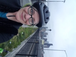 White woman wearing black bike helmet, blue glasses, black jacket with blue top beneath. Skyline of Seattle in the background. Sky somewhat misty.