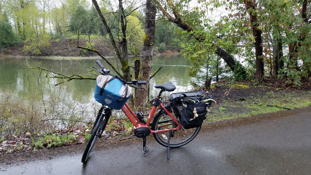 Peach-colored electric bike parked on a trail with a river and trees in the background. Blue and silver bag on the front handlebars, black bag on the back rack. It's spring and trees are leafing out.