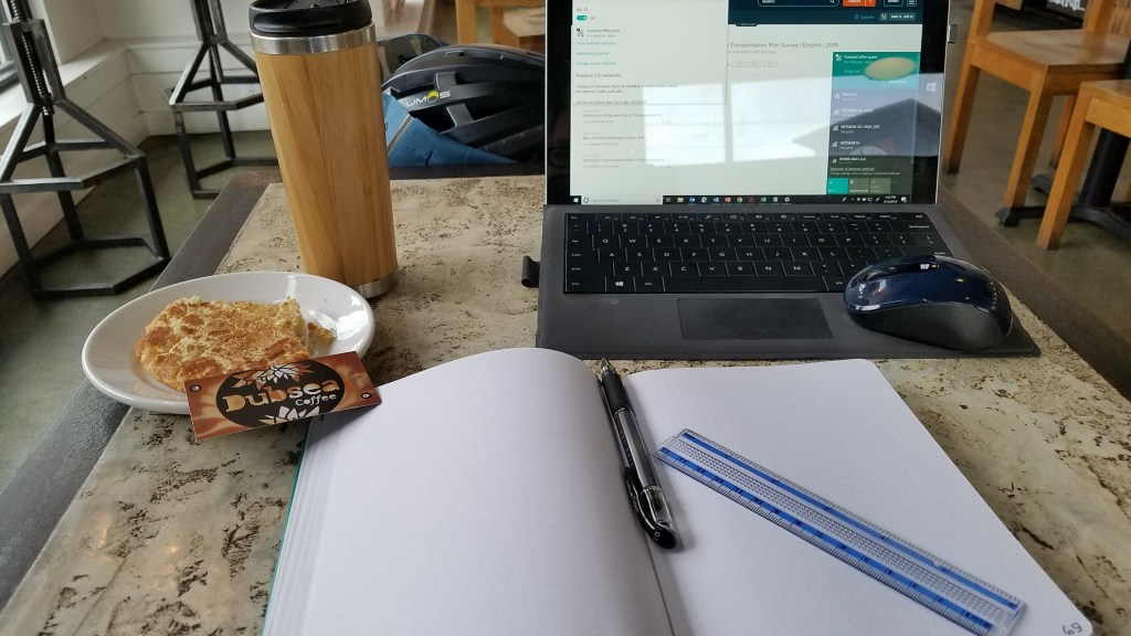 Close-up shot of a table in a coffee shop. Foreground: Open journal with pen and short seethrough plastic ruler with blue markings. Back right: surface tablet with keyboard, open with mouse sitting on the keyboard. Back left, light bamboo coffee go-cup with silver base. At left, small white plate with a giant snickerdoodle minus a few bites, and a business card reading Dubsea Coffee.