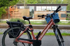 Peach e-bike in foreground with big medium blue handlebar bag, black pannier on back rack far side. Across the rialroad tracks and street, brick and glass building. Left side of building in orange metal, a face with words underneath Chief Seattle Is Watching. At right, building name in whit eletters, Duwamish Longhouse & Cultural Center.