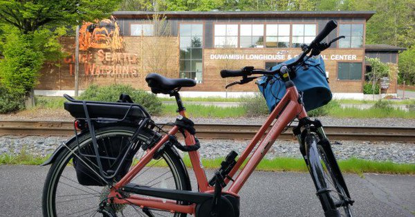 Foreground: Closeup of peach e-bike with medium blue front handlebar bag, black pannier on back rack. In background. side of Duwamish Longhouse with signage and image of Chief Seattle.