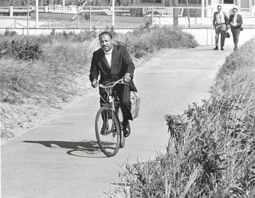 Black and white photo of Dr. Martin Luther King, Jr. riding a bicycle on a path wearing a suit and his clerical collar. Two men in suits in background.