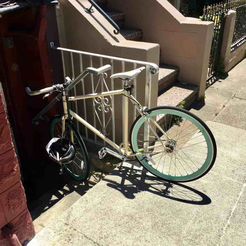 A bicycle locked to a metal gate halfway down some stairs. It has bullhorn handlebars and a helmet clipped to the lock. And very pretty tiffany blue rims.