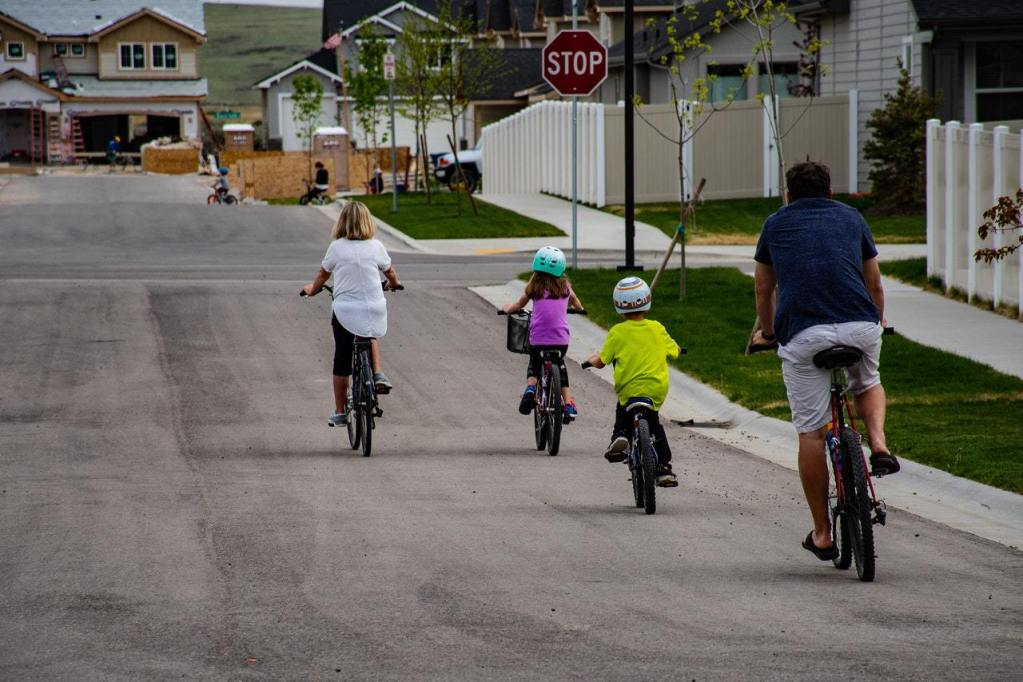 A family riding their bicycles in a suburban neighborhood.