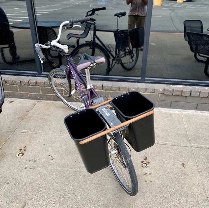 a bicycle with 2 trashcans attached to the sides of a rear bike rack in a DIY fashion