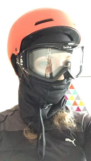 A bike commuter wearing the most serious face protection with a balaclava, clear ski goggles, and a helmet on top.