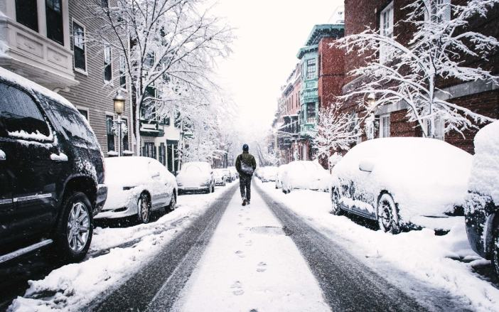 A snow covered street with tire tracks and fresh snow in the middle. Someone is walking through the fresh snow.