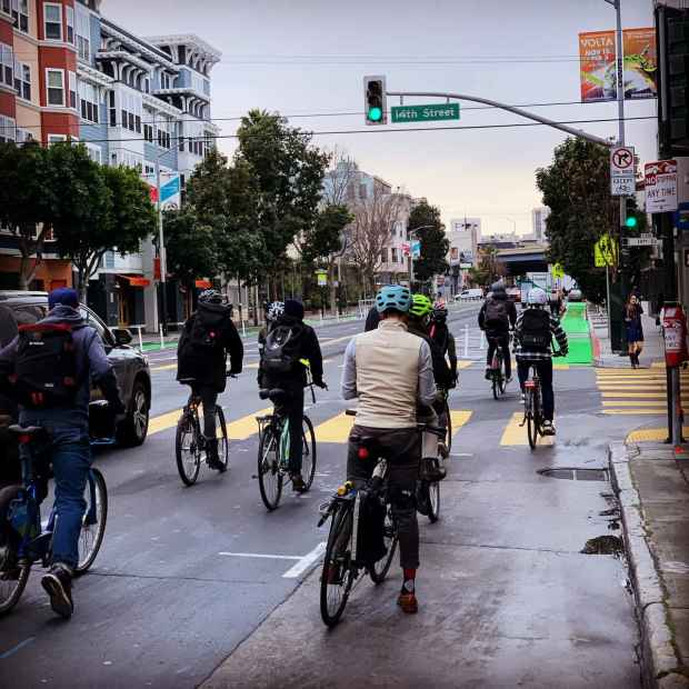 A crowd of bicycles going through a green light on Valencia Street in San Francisco.