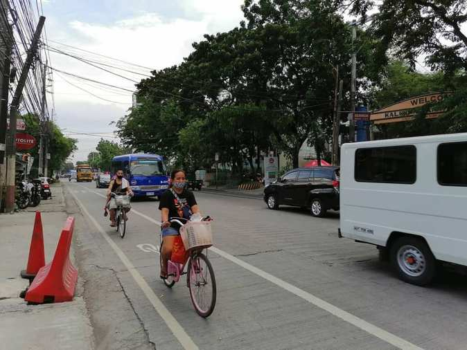 A few bike commuters using the bike lane in manila to travel safely.