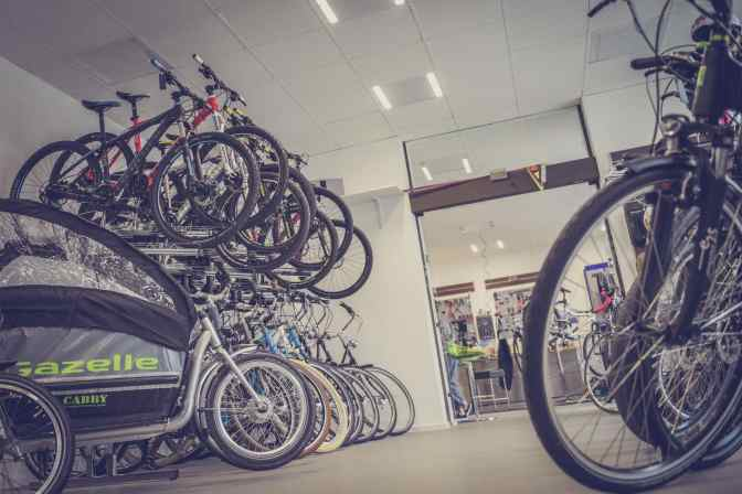 Many bicycles in a local bike shop. Mountain bikes above, city bikes on ground level, and a few cargo bikes. Here you can buy new bicycles, and maybe some used bikes too.