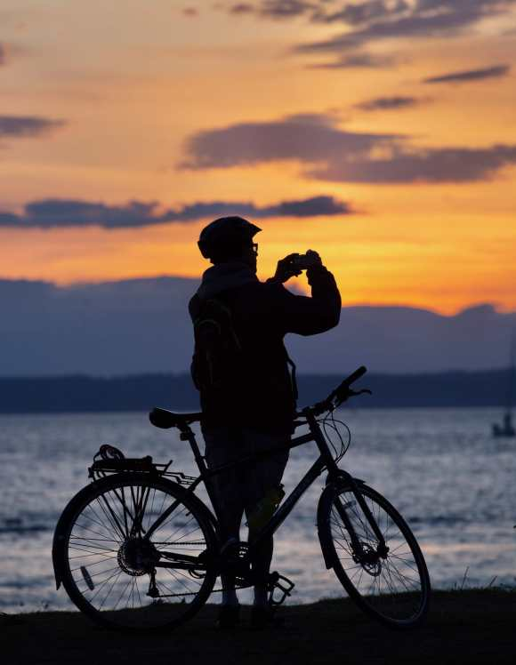 A beautiful sunset with a bicyclist in the foreground at Golden Gardens Park.